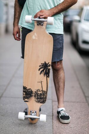 a man holds a longboard in her hands.