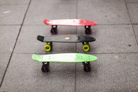 Three skateboards stand on the pavement. Red, black, green skateboard. 스톡 콘텐츠