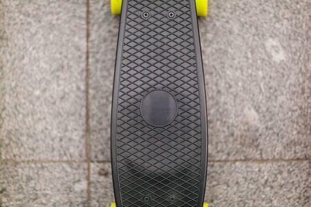 Black skateboard stands on the sidewalk. close-up