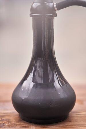 Dark glass hookah flask close up.