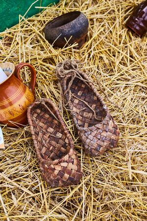 Bast shoes on the straw at the souvenir market. Traditional shoes in Russia.