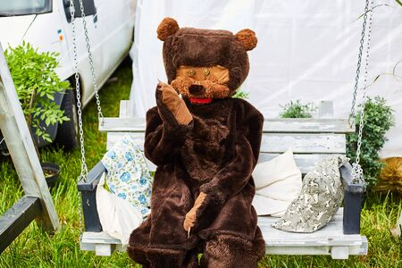 A man in a bear costume on holiday waves his paw. Bear on a swing. 스톡 콘텐츠