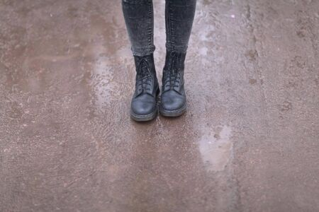 Female legs in black boots close up.