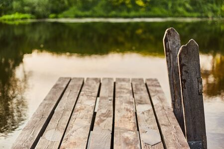 Wooden pier on the river. Descent to the water. Stock Photo