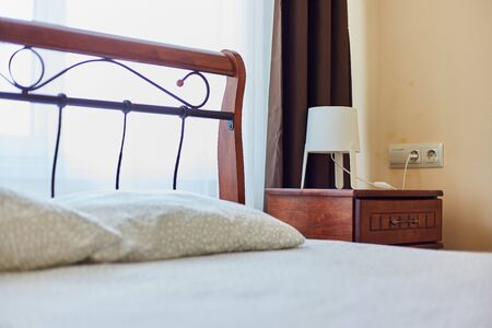 A tucked-in bed with a bedside table indoors Stockfoto