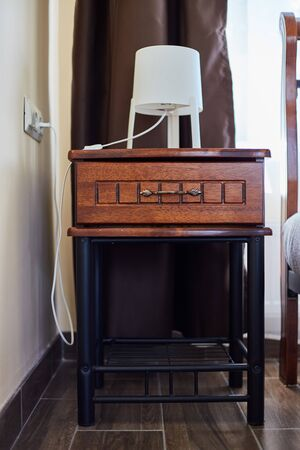 A bedside table made of wood with a lamp. Hotel Interior