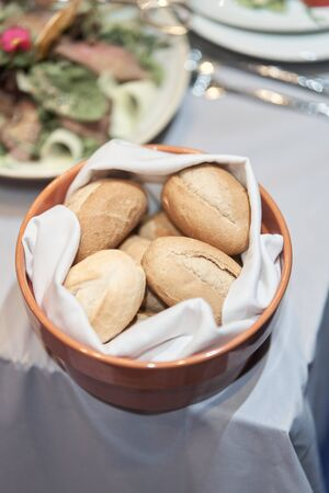 Small bread on a dish. Event table setting.