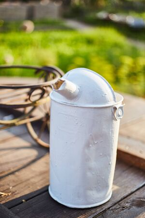 Old iron white watering can stand on a wooden well lid.