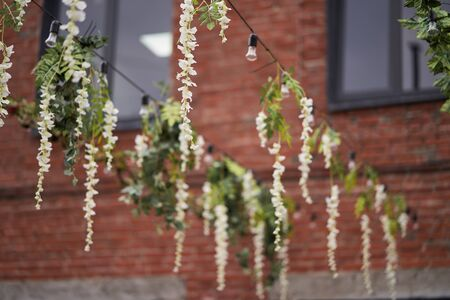 Artificial flowers are white hanging. Decor Garlands of flowers.