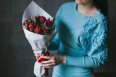 A bouquet of red flowers in the hands of a woman.