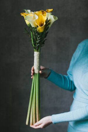 A bouquet of yellow callas in the hands of a woman.