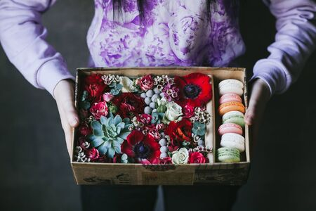 Colorful handmade macaroons in a gift box with flowers.