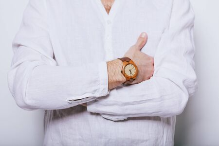 A man in an elegant white shirt with a clock on his hand. Stockfoto