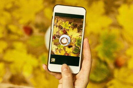 A girl photographs an autumn flatlay on her phone. Autumn flat lay composition with dry leaves wreath frame and coffee latte cup on wooden background Imagens - 134731773