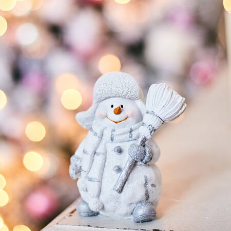 Snowman toy on the background of a Christmas tree and garlands. Bokeh. Stock Photo