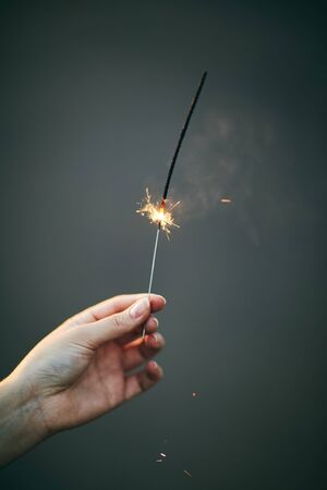 A girl holds a sparkler in her hand. New Year. Stock Photo