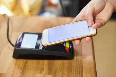 Contactless payment method. The girl applies the phone to the banking terminal. Female customers using the cell phone to pay for goods. Stock Photo