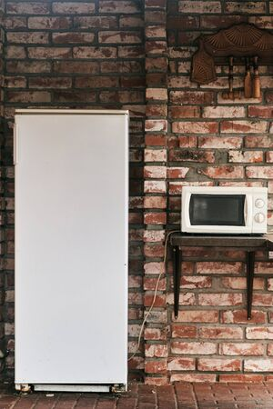 Fridge and microwave in the courtyard of a brick house. Stock Photo