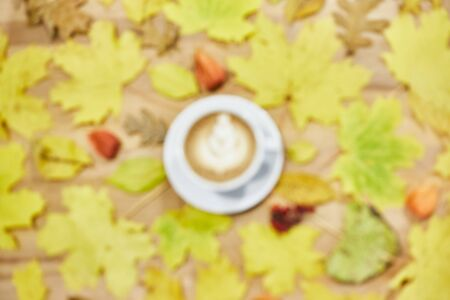 Autumn flat lay composition with dry leaves wreath frame and coffee latte cup on wooden background. Creative autumn. Top view, copy space