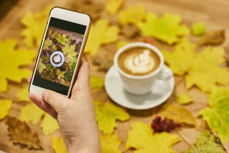 A girl photographs an autumn flatlay on her phone. Autumn flat lay composition with dry leaves wreath frame and coffee latte cup on wooden background