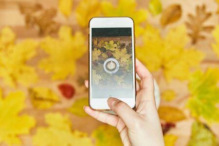 A girl photographs an autumn flatlay on her phone. Autumn flat lay composition with dry leaves wreath frame and coffee latte cup on wooden background Imagens - 134732305