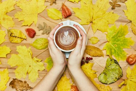 Autumn flat lay composition with dry leaves wreath frame and coffee latte cup in woman hand on wood background. Creative autumn thanksgiving, fall, Halloween concept. Top view, copy space Stock Photo