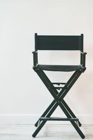 Black directors chair against a white wall. Makeups chair.