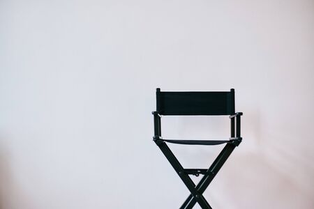 Black directors chair against a white wall. Makeups chair. Banner. Copy text.