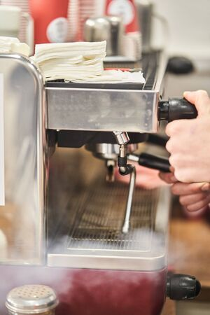 Barista making a hot drink in a coffee shop. Barista is making coffee. close-up