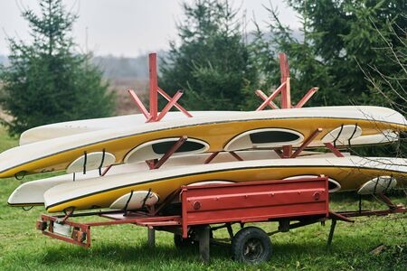 Multi-colored kayaks loaded on a trailer. River Tourism. Stock Photo