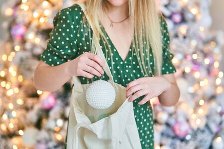 A young woman takes a ball out of a bag. Giving and receiving a present.