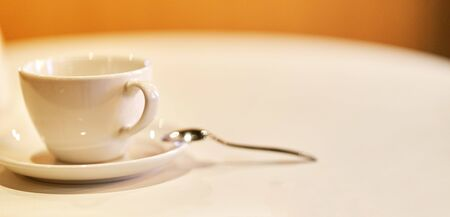 White coffee cup with saucer and spoon close up.