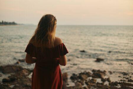 Girl admires the sunset on the beach. India, Northern GOA, Arambol.