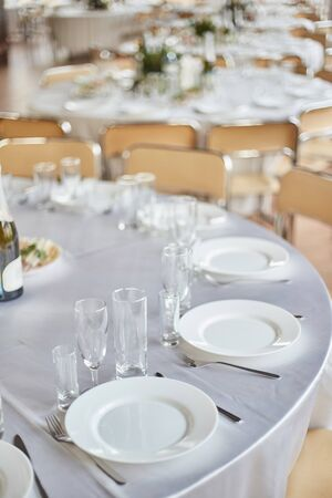 Table set for an event party or wedding reception. Banquet table design. Festive table setting. Glass and plates on the table
