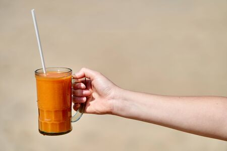 A girl holds a glass with freshly squeezed papaya juice. Hand close-up.
