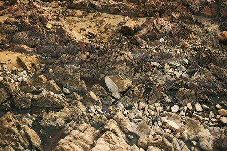 The rocky texture on the ocean. Goa coast, Arambol.
