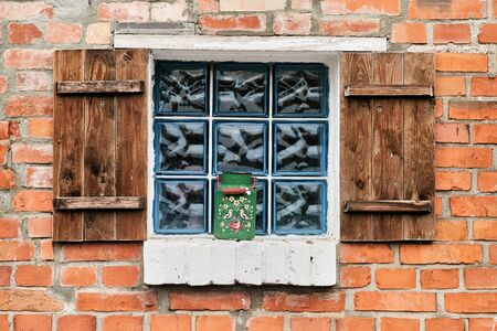 Stained glass window with wooden doors in a brick house.