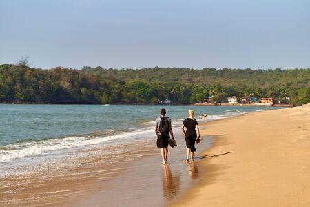 A young couple walking along the beach in Goa. Querim beach.