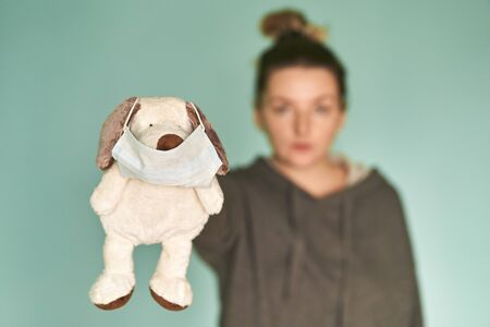 The girl holds a soft toy in her hands. Soft toy with a medical mask. Coronavirus. Viral Disease Prevention