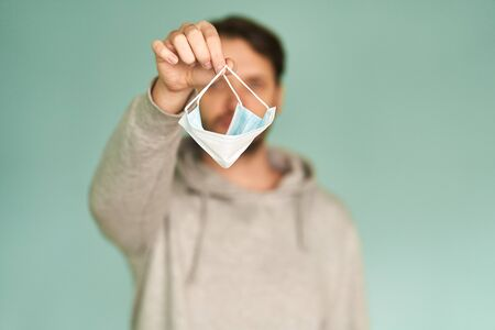 The man holds a medical mask in his hands. Coronavirus. Prevention of viral diseases.