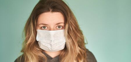 Girl in a medical mask on a green background. Coronavirus. Prevention of viral diseases. Banner.