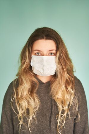 Girl in a medical mask on a green background. Coronavirus. Prevention of viral diseases.