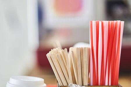 Colored plastic tubules for drinks. Wooden sticks for stirring drinks. Imagens