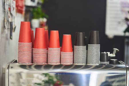 Red and black paper cups for coffee. Imagens