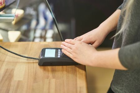 A girl enters a pin code at a bank terminal in a cafe. Credit card payment. Financial security. Acquiring