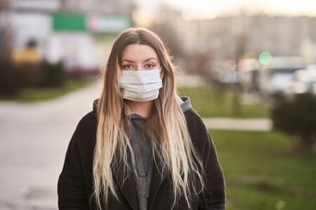 Girl in a medical mask on the background of the city. Coronavirus. Prevention of viral diseases.