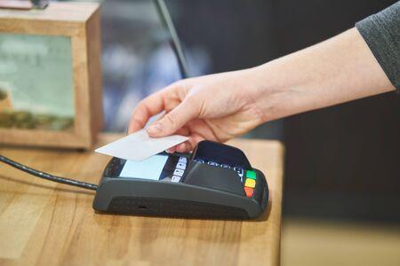 Contactless payment method. The girl applies a credit card to the banking terminal. A girl customer use a credit card to pay for goods. Imagens