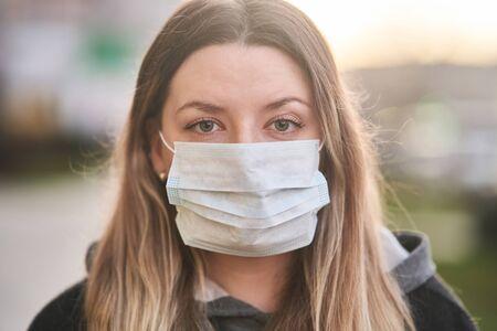Chica con una máscara médica en el fondo de la ciudad. Coronavirus. Prevención de enfermedades virales.