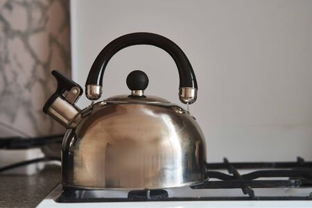 Iron gray kettle stands on a gas stove. Stockfoto