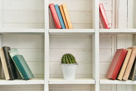 White wooden shelves with old books. Wooden bookcase.